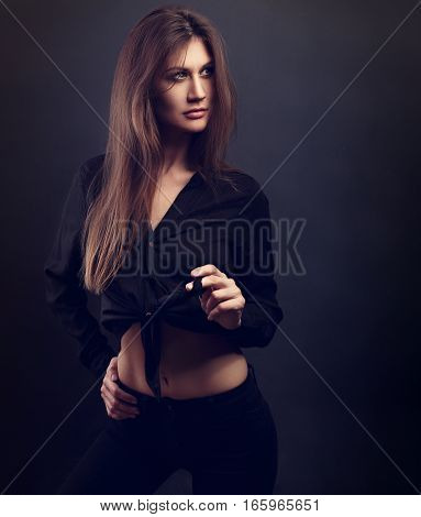 Sexy Female Slim Model Posing In Black Shirt And Black Jeans With Long Hair Style On Dark Background
