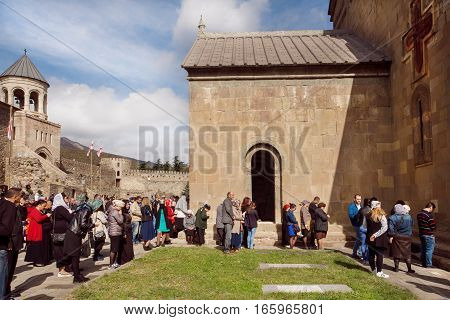 MTSKHETA, GEORGIA - OCT 14, 2016: People praying near the historical walls of the christian Svetitskhoveli Cathedral, built in 4th century on October 14, 2016. UNESCO World Heritage Site.