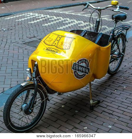 AMSTERDAM, NETHERLANDS - JANUARY 04, 2017: Parked in city street bicycle close-up. On January 04, 2017 in Amsterdam - Netherlands.