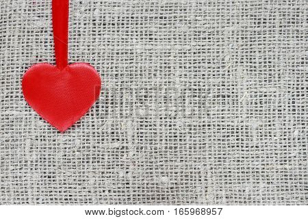 red satin heart on a string rests on a linen background