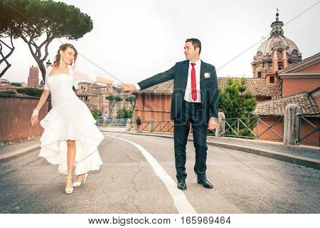 Newlyweds, hands in hands. Happy and joyful married couple in Rome's historic center. Italy