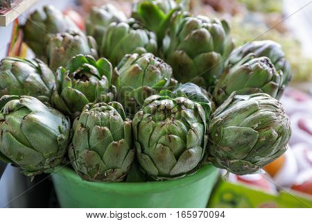 Fresh artichokes for sale at farmer's market. Horizontal. Daylight. Close up.