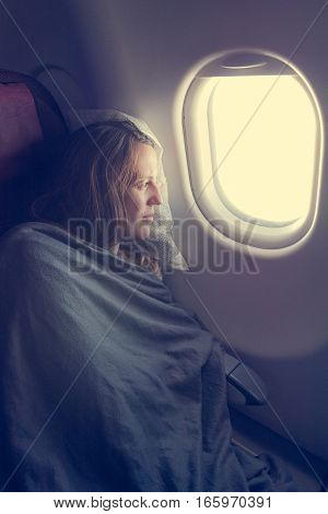 Female passenger sleeping covered with blanket. Comfortable flying.