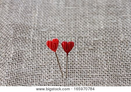 two red little hearts on the background of linen fabric