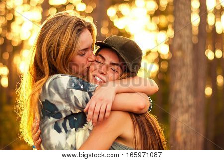 Beautiful girl hugging on bokeh background in the forest.