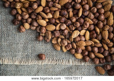 pile of almond nuts and hazelnuts on a gray cloth of burlap. view from above