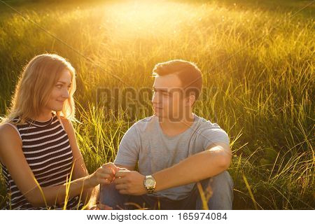 A portrait of young beautiful couple sitting on grass field holding hands looking at each other with great love enjoing nice summer weather. Young couple in love over green background. Summer time