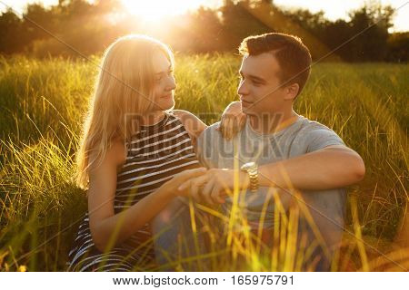A photo of young couple sitting on the grass looking at each other with love holding each other`s hands relaxing outdoors. Romantic concept. Happy young couple. Summer time sunshine nice weather