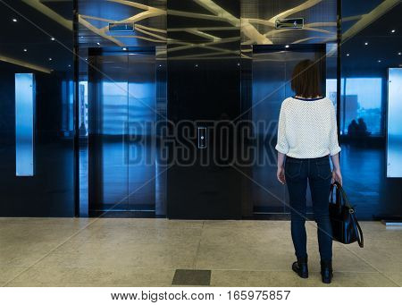 Woman is standing in front of the metal doors of the elevator