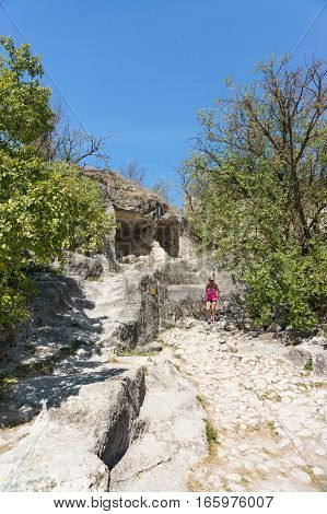 BAKHCHISARAY REPUBLIC of CRIMEA RUSSIA - SEPTEMBER 13.2016: A tourist inspects monastic cells in the rock. The medieval town-fortress Chufut-Kale