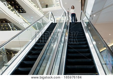 Woman is going down the escalator in the mall