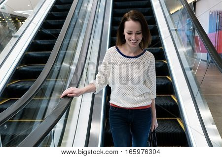 Smiling woman is going down the escalator