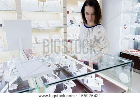woman is looking at jewelry under glass case in store