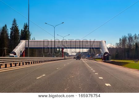 View Novopriozerskoe highway with cars traffic lights and overhead pedestrian crossing against a blue sky.