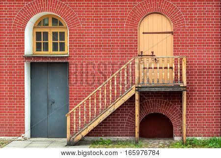 Door window with arch and stairs and against the wall of red brick. From the series window of Saint-Petersburg.
