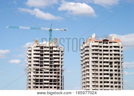 Two construction buildings and big hoisting tower crane