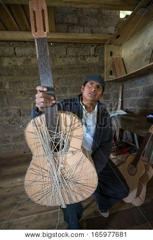 July 22 2016 San Bartolome Ecuador: an indigenous luthier holds up an unfinished guitar in his small rural shop