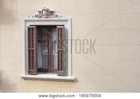 Ornamented Window with Wooden Shutters on Yellow Wall