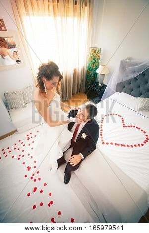 Newlyweds in bedroom with heart. Just married. First night. On the bed rose petals heart-shaped.