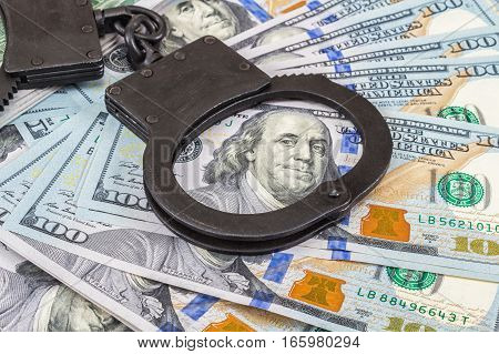 Steel police handcuffs lying on the background of american dollars