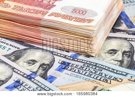 Stack of five thousandths banknotes of russian roubles and american dollars close up