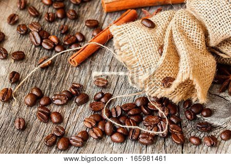 Roasted coffee beans , coarse burlap sac and cinnamon on old wooden table. Top view, grunge texture