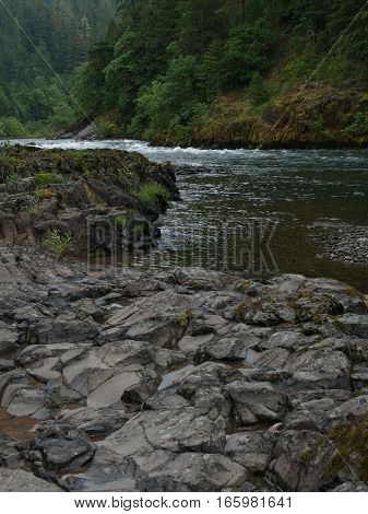 The pure rock banks of the North Umpqua River in Douglas County in Western Oregon have some bushes trees and moss growing on a summer day.