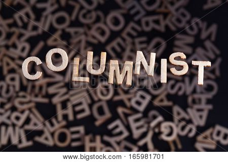 Columnist wooden letters created in wood floating above random letters below out of focus on a black background