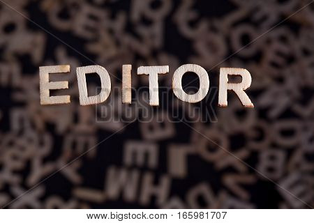 Editor wooden letters created in wood floating above random letters below out of focus on a black background