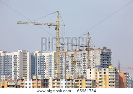 Yellow hoisting tower cranes construction city buildings and residential houses
