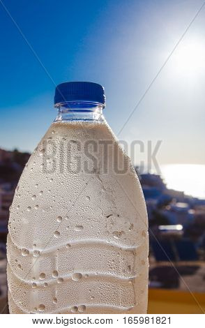 Water bottle with drops on the city and sea background and the sun
