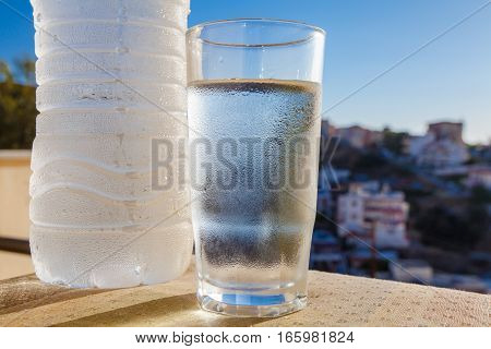 Water bottle full of water with drops and glass on the city and sea background and the sun. Village Bali. Island Crete. Greece.