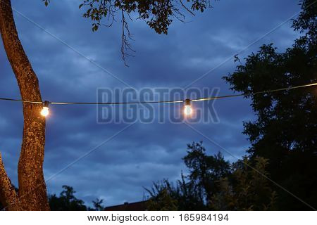 String lights in a sommer party with rainy clouds
