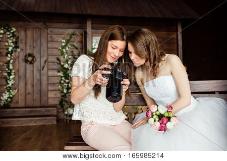 Young sexy photographer shows the bride had just taken photos