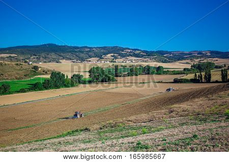 Tractor plowing field with green trees on it in Spain