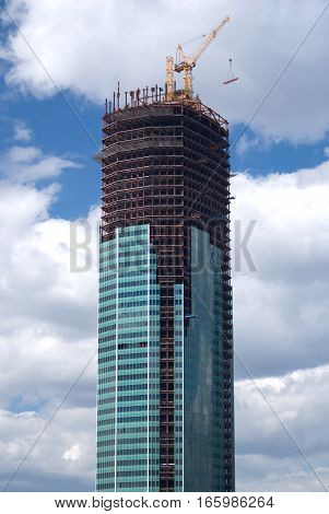 Yellow hoisting tower crane on top of high construction building vertical view