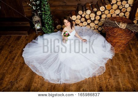 Young sexy bride in the studio is sitting on the wooden floor
