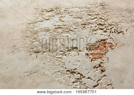 old plastered wall with cracks and bricks