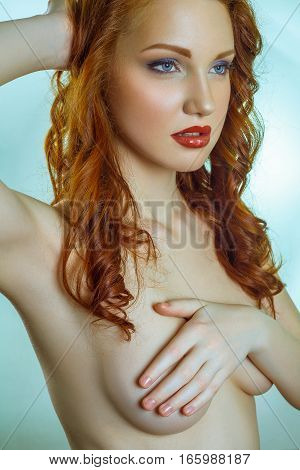 Portrait of naked beautiful fashion model with red curly hair, makeup and red lips on blue background. full of emotion covering her chest with hand on head.