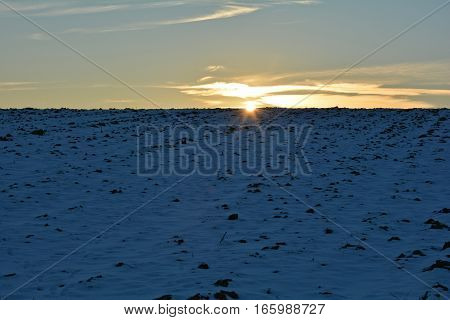 Snowy field at the sundown with clouds