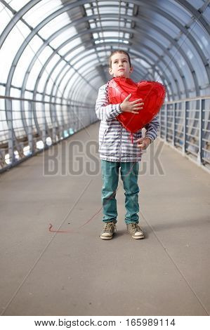 dreamy boy with red heart in hands. kid with a red balloon as an heart. the concept of Valentine's day