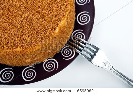 whole cream cake on the plate and fork close up