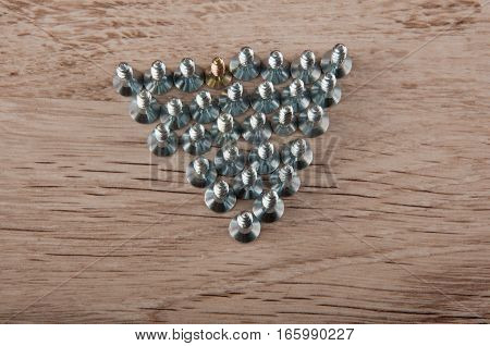 Top. view. Group of metallic screws stay in triangle shape on wooden table