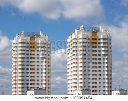 Front view of two white constructed buildings over beautiful blue sky with clouds
