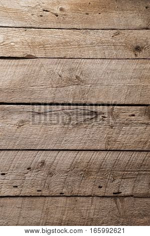 Rough wooden boards inside an old outbuilding with saw marks and horizontal arrangement
