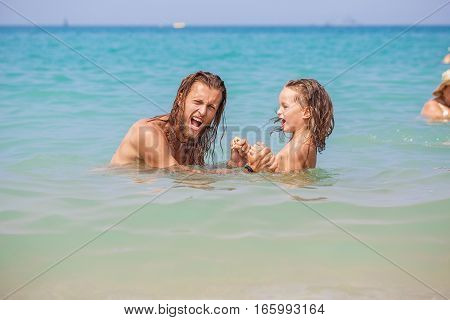 Father and son are having fun in the sea