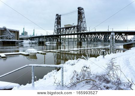 Snow covered boat on the Willamette River with the Steel Bridge in the background in Portland Oregon