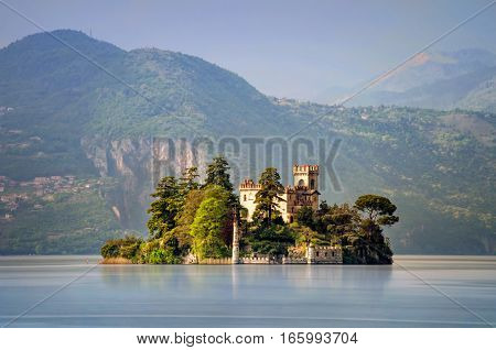 Little island Isola di Loreto on Iseo Lake with mountains in background Italy