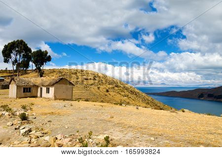 Small hosue on the Island of the Sun with Lake Titicaca visible in the background in Bolivia