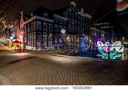 AMSTERDAM NETHERLANDS - JANUARY 07 2017: Night streets of Amsterdam with blurred silhouettes of passersby on January 07 2017 in Amsterdam - Netherland.